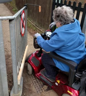 Disabled person opening gate