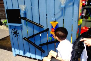 A child reaches towards a brightly coloured activity wall