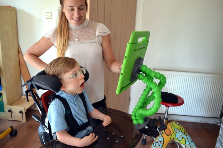 A small boy in a wheelchair looks intently at a bright green tablet holder