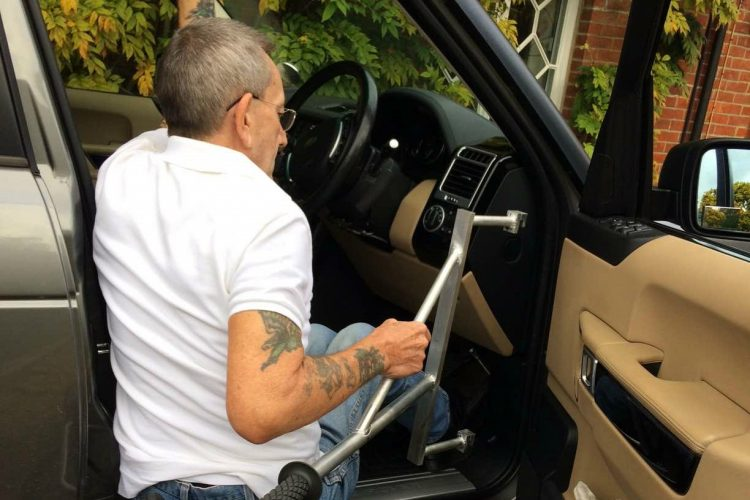 A man uses a metal handle to climb into the driving seat of a four by four