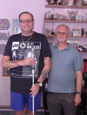 Two smiling men are standing side by side. The taller man is wearing a black Star Wars t shirt and holding a white cane.