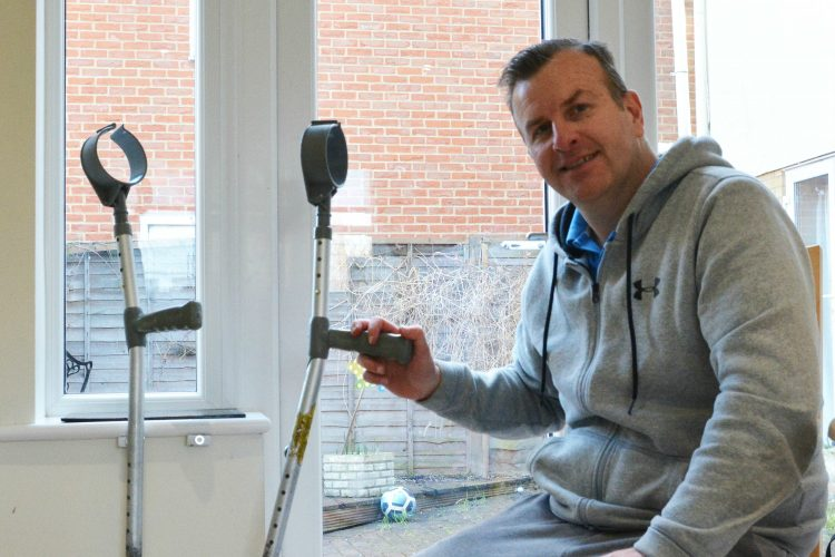 A smiling man holding a crutch. The other is propped by a window