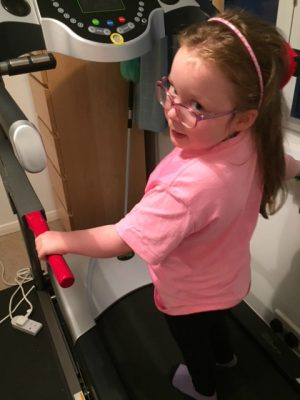 a child stands on a treadmill
