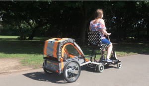 a lady rides her scooter pulling a trailer