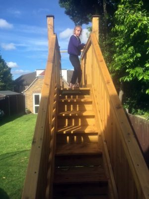 A girl stands at the top of a wooden slide
