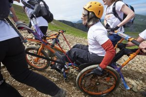 A lady in a yellow helmet and sporty looking wheelchair climbs a steep gravel path