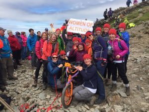 A team of happy women in outdoor gear holding a sign that reads 'Women of Altitude'