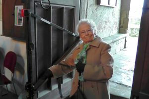 A smiling lady uses the handrail to go down some old steps