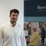 A man stands smiling in front of a Remap banner
