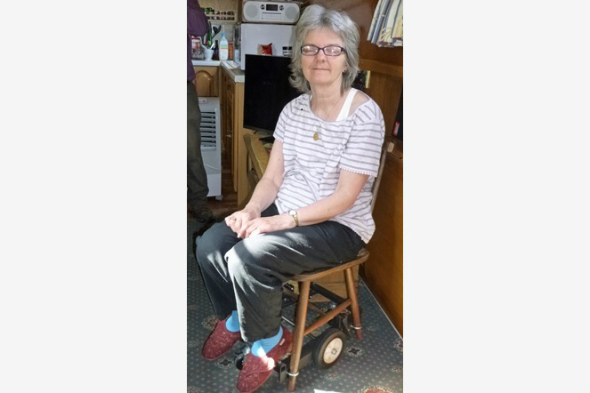 A lady with grey hair and glasses sits on a wooden stool