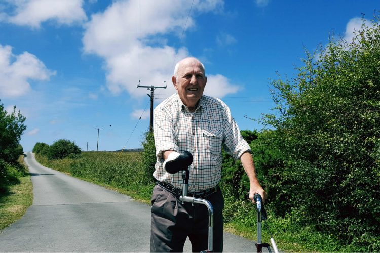 A man with one arm uses a rollator to walk down a country lane