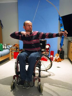 A man in a wheelchair aiming a large archery bow