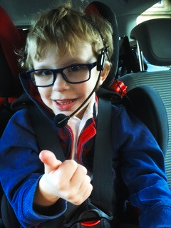 A small boy wearing a headset gives a thumbs up to the camera