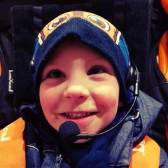 A small child wearing a headset smiles at the camera