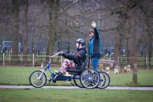 A boy in the park riding a trike. A lady on the trailer behind him waves at the camera