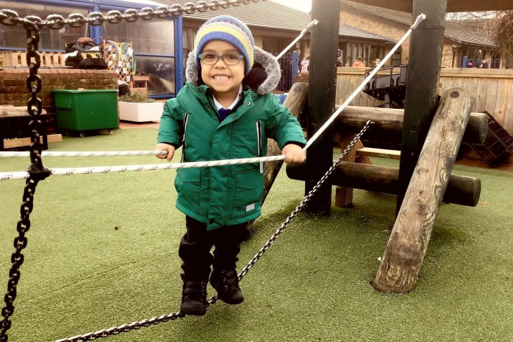 A smiling boy balancing on playground apparatus