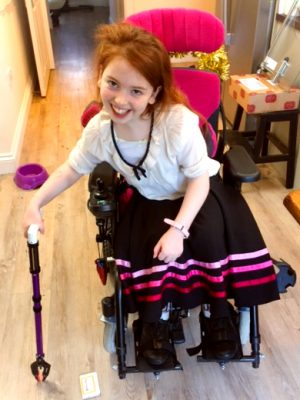 A happy girl in a pink wheelchair holding a purple reacher