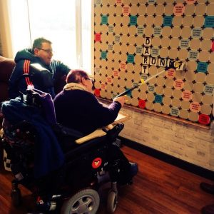 Two people in wheelchairs using reachers to place giant Scrabble tiles