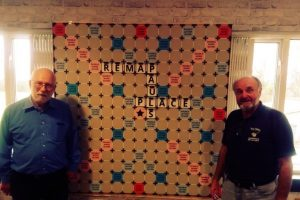 Two men stand either side of a giant scrabble board