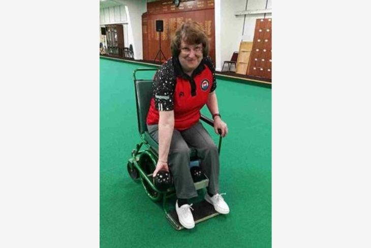 A smiling lady sits in her bowling wheelchair. She is about to make a shot.