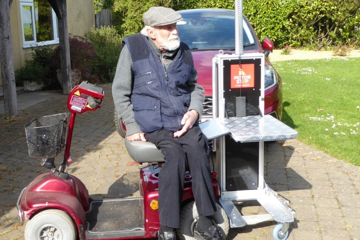 Geoff sits on his mobility scooter next to his new lift
