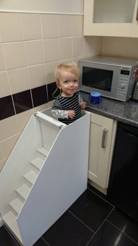 A small, grinning boy stands on a set of white steps next to a microwave
