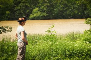 Emmy wearing her binoculars looking out across a river