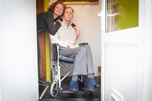 A man in a wheelchair is hugged by a lady as they look through a doorway