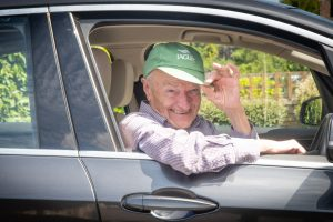 A man leans out of the window of his car and tips his hat