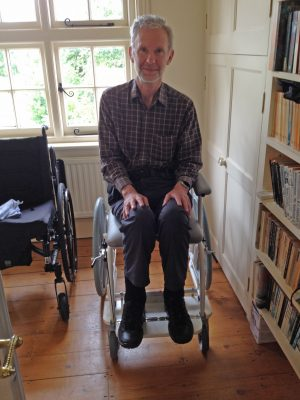 A man sits in a wheelchair and smiles at the camera