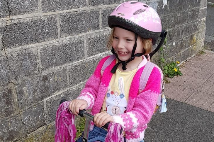 A smiling girl with a pink cycle helmet