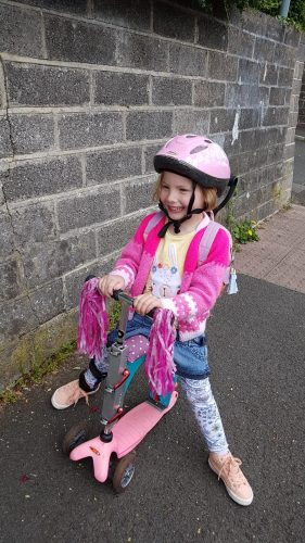 A smiling girl wearing pink rides a pink scooter with pink streamers on the handlebars