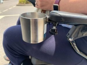 A silver cup holder clipped to the arm of a wheelchair