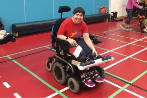 Rachel reaching for her boccia balls which are held at the front of her powerchair