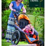 mum pushing smiling son in wheelchair