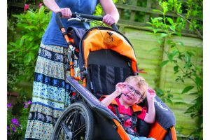 mum pushing smiling son in wheelchair