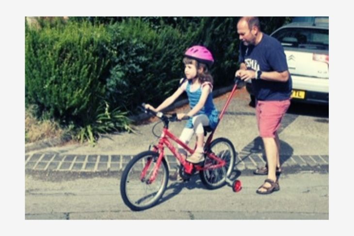 A girl in a pink helmet rides a red bike, with Dad running behind