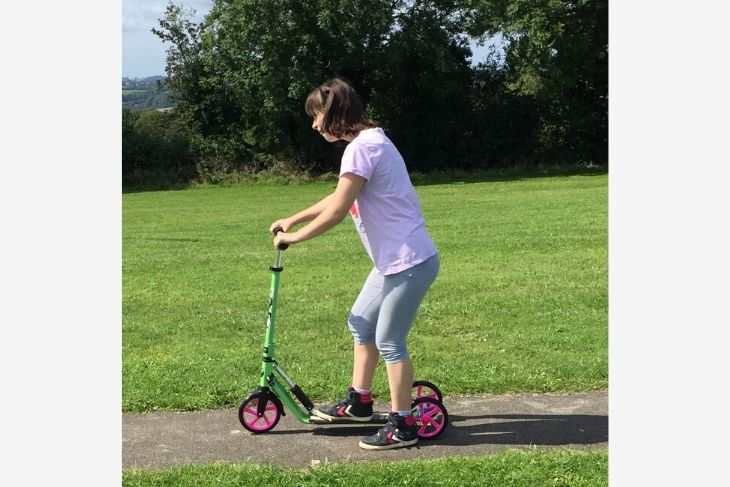 Alice rides her scooter through the park. It is lime green with bright pink wheels.