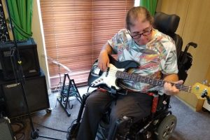A man sits in a powerchair and plays an electric bass guitar