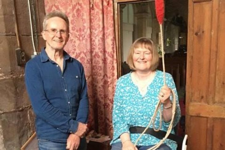 Terry stands next to Helen, who is sitting on her new stool and holding a bell rope