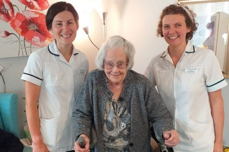 Nan stands smiling between her physio and her OT