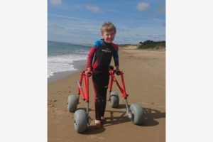 Thomas on the beach wearing a wetsuit, holding his red walker and grinning at the camera
