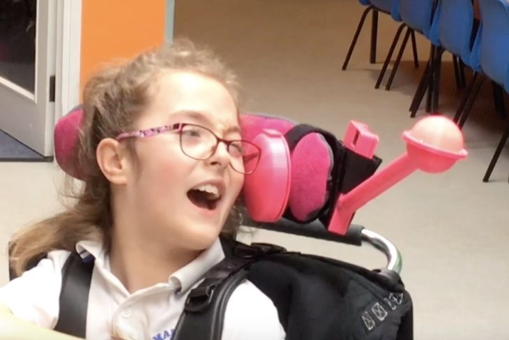 Lucie and her new gadget - a pink light on her wheelchair headrest